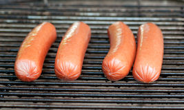 Fresh hot dogs on grill Royalty Free Stock Images