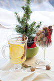 Fresh hot green tea in glass cup with lemon and cinnamon, chocolate cakes in basket and nuts and cinnamon Royalty Free Stock Images