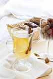 Fresh hot green tea in glass cup with lemon and cinnamon, chocolate cakes in basket and nuts and cinnamon Stock Photos