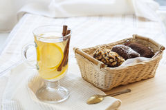 Fresh hot green tea in glass cup with lemon and cinnamon, chocolate cakes in basket and nuts and cinnamon Royalty Free Stock Image