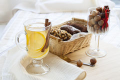 Fresh hot green tea in glass cup with lemon and cinnamon, chocolate cakes in basket and nuts and cinnamon Royalty Free Stock Photo