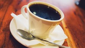 Black coffee in white cup on the brown wooden table Royalty Free Stock Photo