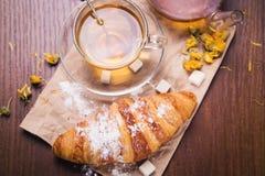 Fresh hot tea with croissant Stock Photos