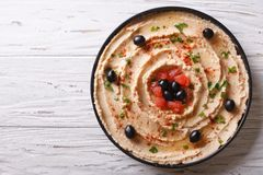 Fresh hummus with olives and tomatoes. horizontal top view Royalty Free Stock Images