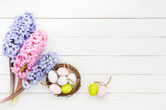 Fresh hyacinths and decorative Easter eggs in small nest on white table. Top view Royalty Free Stock Photos