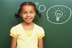 Fresh idea. Portrait of smart girl by the blackboard thinking of light idea and looking at camera Stock Photography