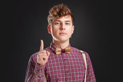 Fresh idea! Attention! Handsome young man in vintage shirt and curly hair keeping finger raised and looking at camera. While standing against black or grey Stock Photos
