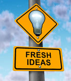 Fresh Ideas. And new innovative solutions symbol with a road and traffic sign with a light bulb on yellow street signage as an icon of successful direction in Stock Image
