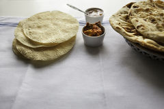 Fresh Indian flat breads Naans and poppadums served on the white cloth Stock Photo