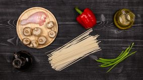 Fresh ingredients for cooking home-made fried noodles on a black rustic wooden table. Top view stock photos