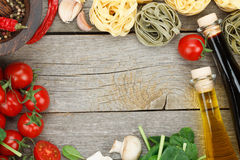Fresh ingredients for cooking. Pasta, tomato and spices over wooden table background with copy space Stock Photo