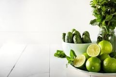 Fresh ingredients cucumber, lime and mint for cooking homemade lemonade. Green vegetables and fruits on a white table. Cucumber, lime and mint on a white royalty free stock images