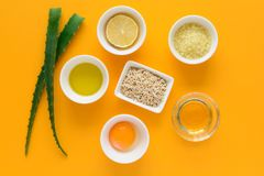 Fresh ingredients for homemade effective acne remedies on yellow background. Honey, sea salt, egg yolk, olive oil, oat, lemon and. Aloe. Flat lay. Copy space royalty free stock photo