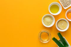 Fresh ingredients for homemade effective acne remedies on yellow background. Honey, sea salt, egg yolk, olive oil, oat, lemon and. Aloe. Flat lay. Copy space stock image