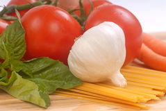 Fresh ingredients for making pasta. Fresh ingredients ready for making homemade spaghetti including tomatoes, garlic, carrots, and basil Stock Photo