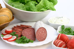 Fresh ingredients ready to make sandwich. Plate of salami with parsley and radish put together with other sandwich ingredients Stock Photography