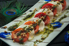 Fresh Italian caprese salad with mozzarella, tomatoes and green basil leaves on white plate Stock Photo