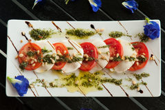 Fresh Italian Caprese salad with mozzarella, tomatoes and green basil leaves on white plate Royalty Free Stock Photography