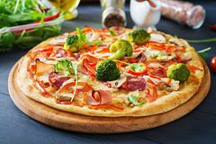 Fresh italian pizza with chicken fillet, mushrooms, ham, salami. Tomatoes, broccoli, cheese on on black background. Italian food stock photography