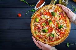 Fresh Italian pizza with chicken fillet, mushrooms, ham, salami royalty free stock photo