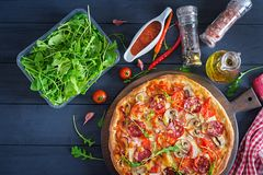 Fresh Italian pizza with chicken fillet, mushrooms, ham, salami royalty free stock images