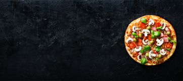 Fresh italian pizza with mushrooms, ham, tomatoes, cheese, olive, basil on black concrete background. Copy space. Homemade with love. Fast delivery. Recipe and Royalty Free Stock Photography
