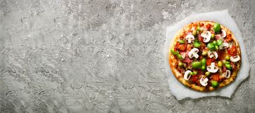 Fresh italian pizza with mushrooms, ham, tomatoes, cheese, olive, basil on grey concrete background. Copy space. Homemade with love. Fast delivery. Recipe and Royalty Free Stock Images