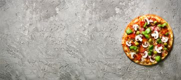 Fresh italian pizza with mushrooms, ham, tomatoes, cheese, olive, basil on grey concrete background. Copy space. Homemade with love. Fast delivery. Recipe and Stock Photos