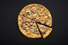 Fresh italian pizza with mushrooms, tomatoes, cheese, on black stone background royalty free stock image