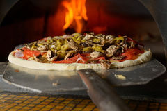 Fresh Italian pizza. Fresh original Italian pizza on a shovel is putting in a traditional wood-fired stone oven Stock Photography