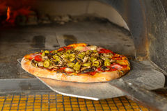 Fresh Italian pizza. Fresh original Italian pizza on a shovel is putting into a traditional wood-fired stone oven Royalty Free Stock Image