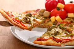 Fresh italian pizza in plate on a surface Royalty Free Stock Images