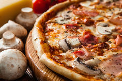 Fresh italian pizza served on wood table close up Royalty Free Stock Images