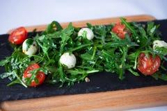 Fresh Italian salad with quail eggs, arugula and tomato with oli Stock Image