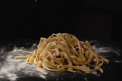 Fresh italian uncooked homemade pasta. Hands making pasta. Spaghetti. Fresh italian spaghetti. Closeup of process of making royalty free stock images