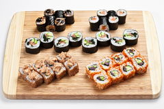 Fresh japanese sushi rolls set on a wooden board. Sushi rolls served on a wooden board background Royalty Free Stock Image
