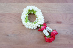 Fresh jasmine and roses garland on timber board Stock Images