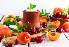 Fresh jogurt with organic ripe apricots and cherries. Food and drink, healthy nutrition concept. Fresh homemade jogurt in a ceramic pot with organic ripe royalty free stock image