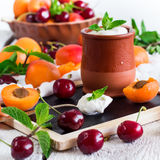 Fresh jogurt with organic ripe apricots and cherries. Food and drink, healthy nutrition concept. Fresh homemade jogurt in a ceramic pot with organic ripe royalty free stock photos