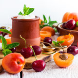 Fresh jogurt with organic ripe apricots and cherries. Food and drink, healthy nutrition concept. Fresh homemade jogurt in a ceramic pot with organic ripe royalty free stock photography