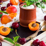 Fresh jogurt with organic ripe apricots and cherries. Food and drink, healthy nutrition concept. Fresh homemade jogurt in a ceramic pot with organic ripe royalty free stock images