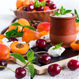 Fresh jogurt with organic ripe apricots and cherries. Food and drink, healthy nutrition concept. Fresh homemade jogurt in a ceramic pot with organic ripe royalty free stock photo