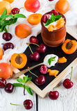 Fresh jogurt with organic ripe apricots and cherries. Food and drink, healthy nutrition concept. Fresh homemade jogurt in a ceramic pot with organic ripe stock images