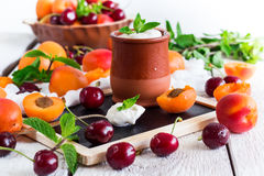 Fresh jogurt with organic ripe apricots and cherries. Food and drink, healthy nutrition concept. Fresh homemade jogurt in a ceramic pot with organic ripe stock photography