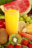 Fresh juice. Fresh orange juice in the middle of fresh fruits Stock Photos