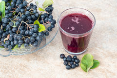 Fresh juice of black chokeberry Aronia melanocarpa in glass and berry in pot on brown ceramic background royalty free stock images