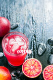 Fresh juice from blood oranges with ice, dark background, space Stock Photos