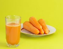 Fresh juice and carrot. Glass with fresh neat juice and carrot on plate Royalty Free Stock Photo