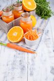 Fresh juice from carrots, orange and lemon. Carrots with leaves and other fresh fruits on a wooden background. Drink in a can, top royalty free stock photo