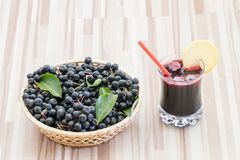 Fresh juice of chokeberry Aronia melanocarpa in glass and berry in pot on wooden royalty free stock photo